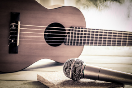 Microphone and acoustic guitar on wooden table in vintage color tone